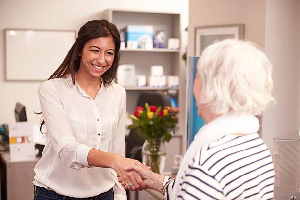 a female physician greeting an elderly woman in the office - receptionist stock photos and pictures