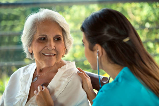Female physician listens to senior patient's heart stock photo