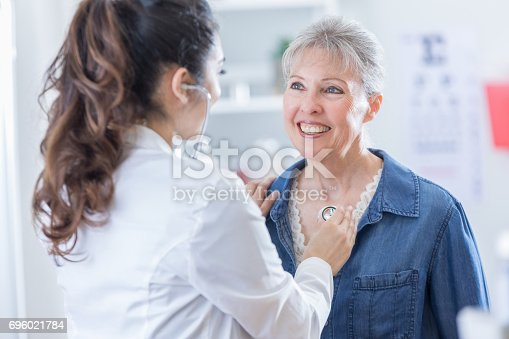 istock Female physician listens to senior patient's heart 696021784