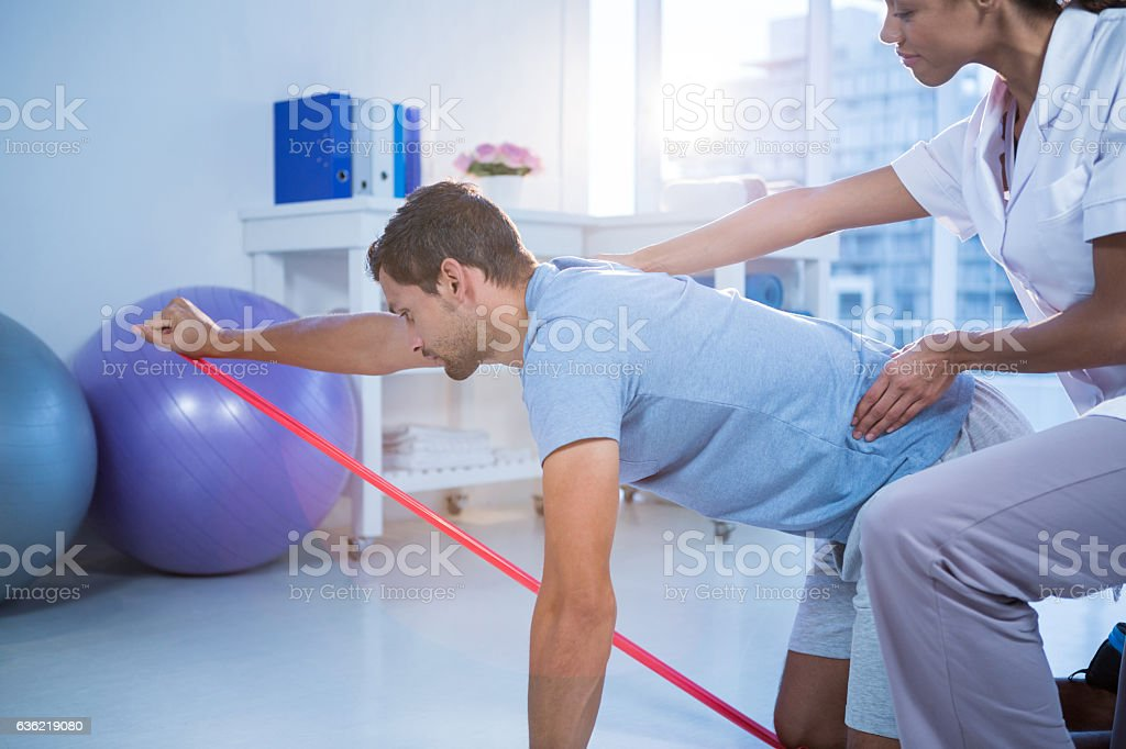 Female physiotherapist assisting a male patient while exercising stock photo