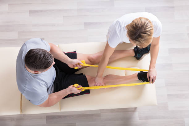 Female Physiotherapist Giving Exercise Treatment stock photo