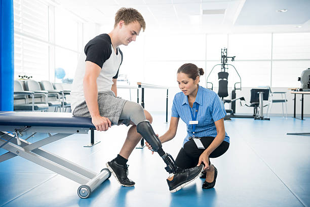 female physiotherapist helping young man with prosthetic leg - australian nurses stock photos and pictures