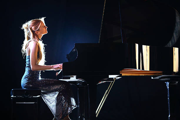 Female pianist in a concert. Side view od adult caucasian woman playing piano in a concert. She's placed on a theatre stage and playing grand concert piano. Wearing elegant long dress. Partially backlit, vertical shot. Black stage curtain in background. pianist stock pictures, royalty-free photos & images