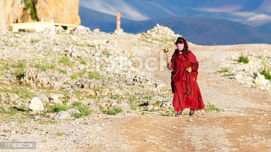 Nam Tso Lake, Tibet / China - Aug 1, 2017: Female pilgrim walking the Kora. Swinging a hand prayer wheel. In the background montains of the Tibetan Plateau with sky and clouds. Tibetan Buddhism.