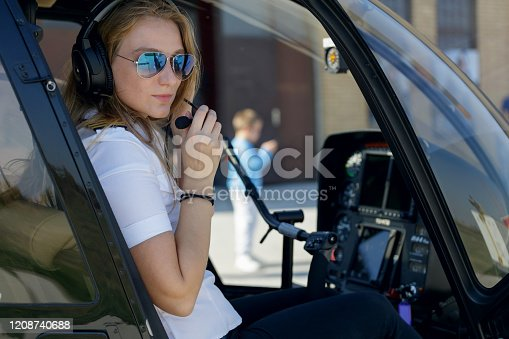 Female helicopter pilot in cockpit with headphones on checking microphone