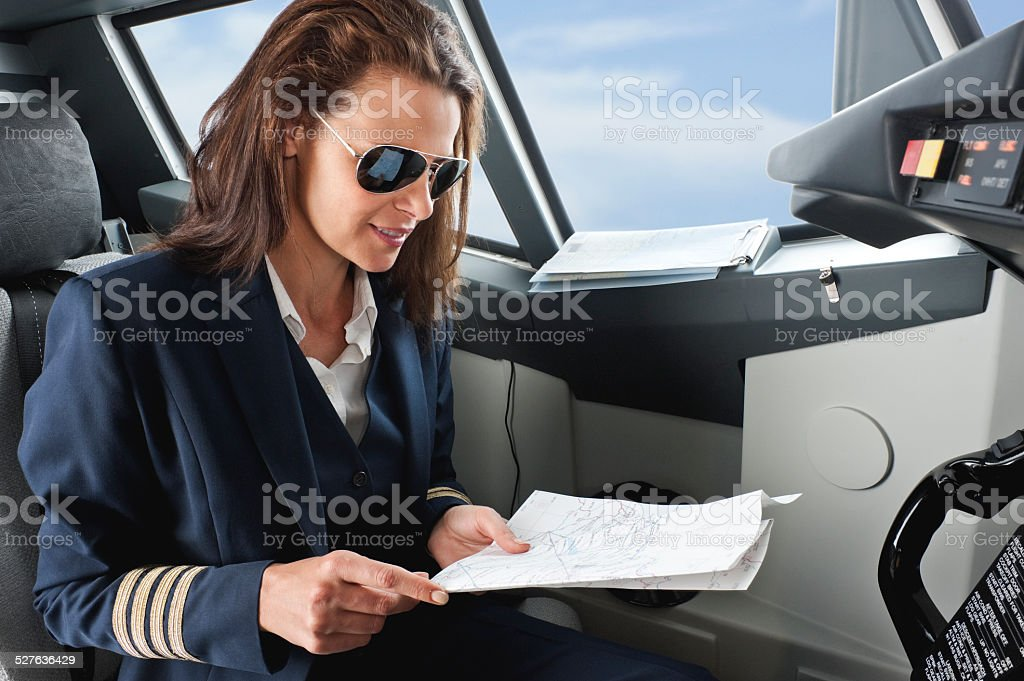 Female pilot with map in airplane cockpit stock photo