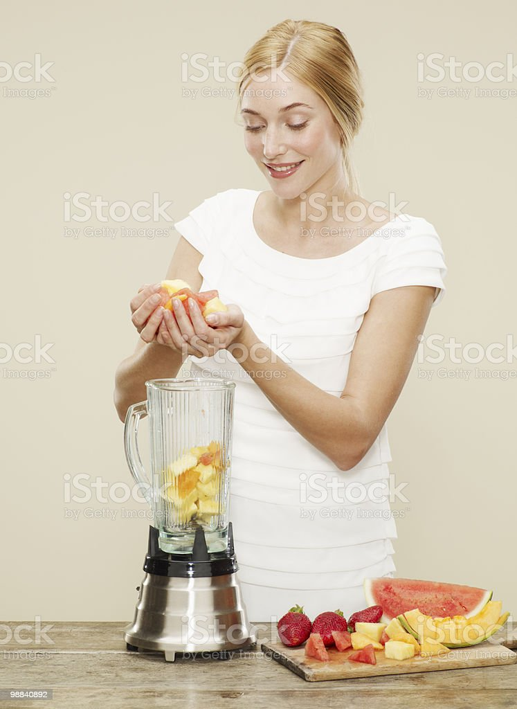 female placing ingredients into blender royalty-free stock photo