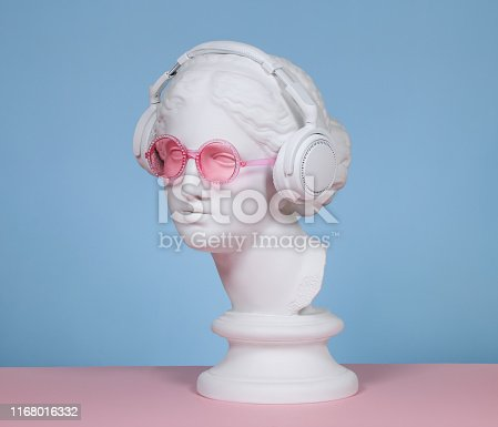 Plaster head model (mass produced replica of Head of Aphrodite of Knidos) wearing headphones and pink eyeglasses
