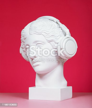 Plaster head model (mass produced replica of Head of an Amazon) wearing headphones