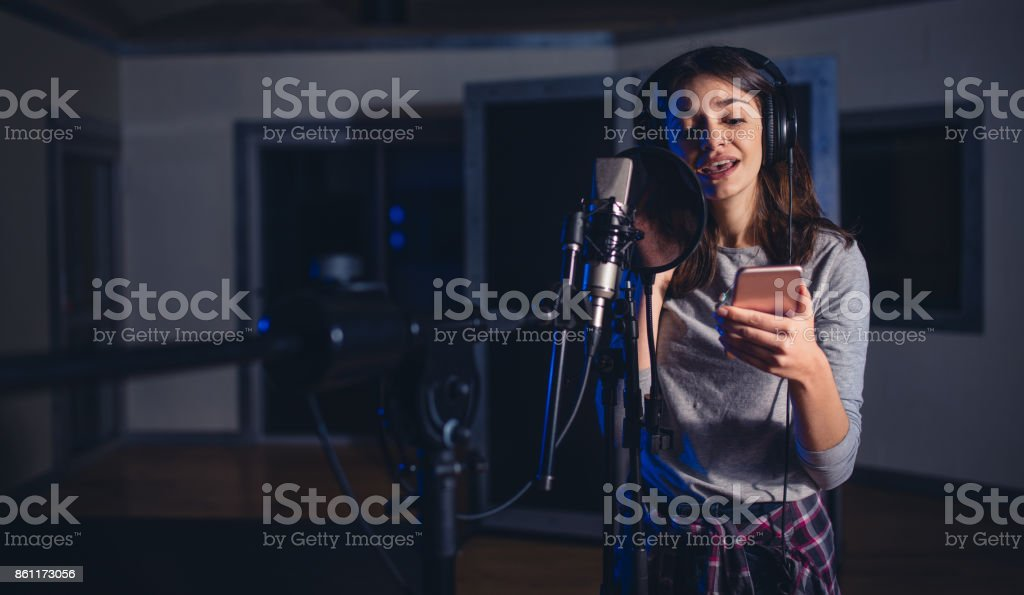 Female playback singer with mobile phone stock photo