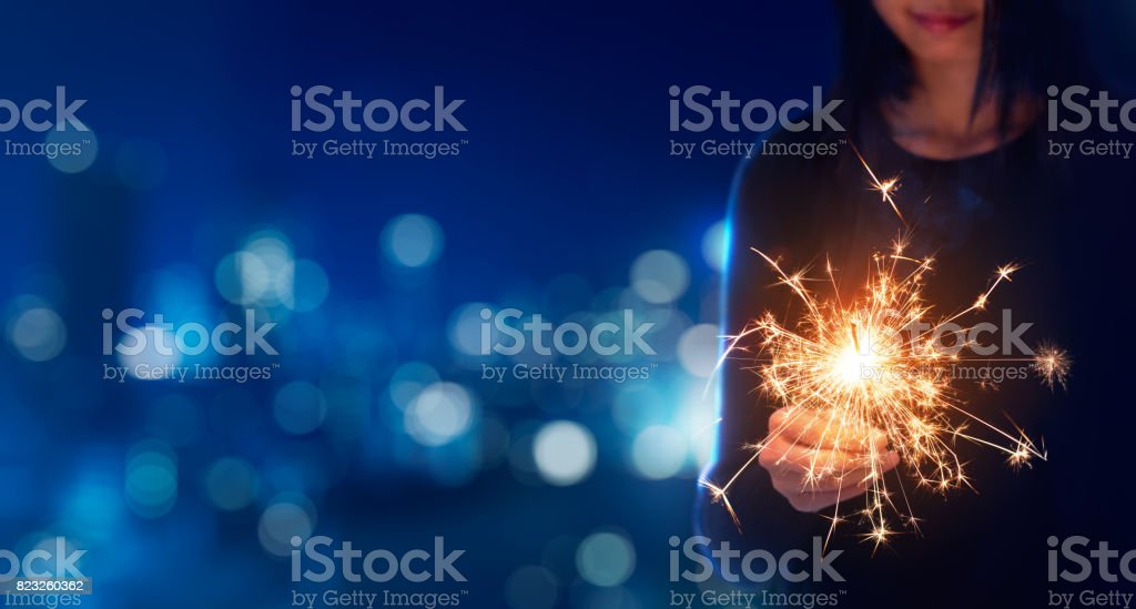 Female playing sparklers during celebration stock photo