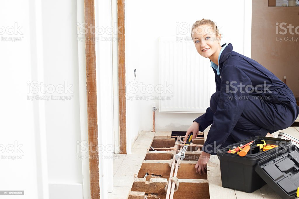 Female Plumber Fitting Central Heating System stock photo