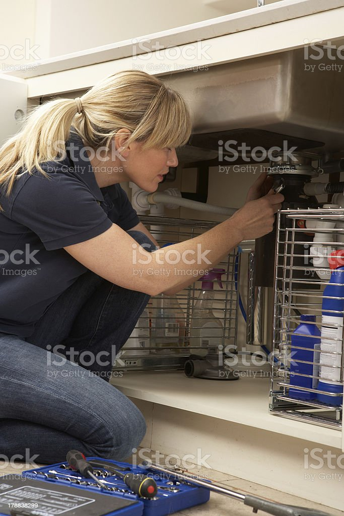Female Plumber Working On Sink In Kitchen stock photo