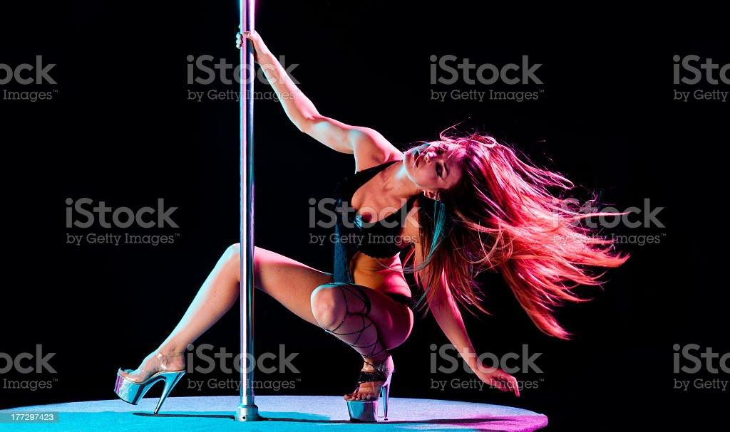 Female pole dancer with long brown hair squatting on podium stock photo