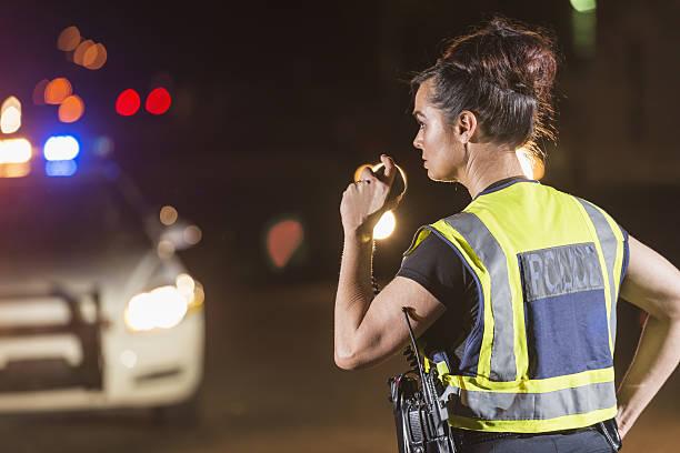 Weibliche Polizist bei Nacht, redet mit radio – Foto