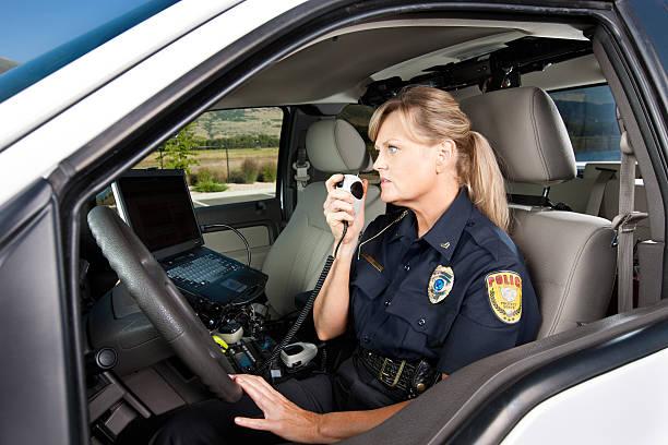 donna poliziotto parlare alla radio nel veicolo - talk in a radio foto e immagini stock