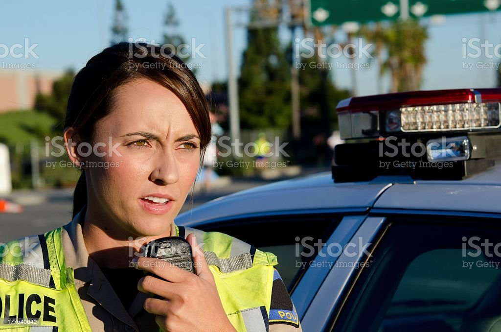 Female police officer talks into her radio outside stock photo