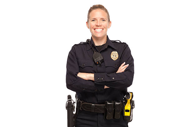 Female police officer with arms crossed Happy female police officer posing with arms crossed against white background police uniform stock pictures, royalty-free photos & images