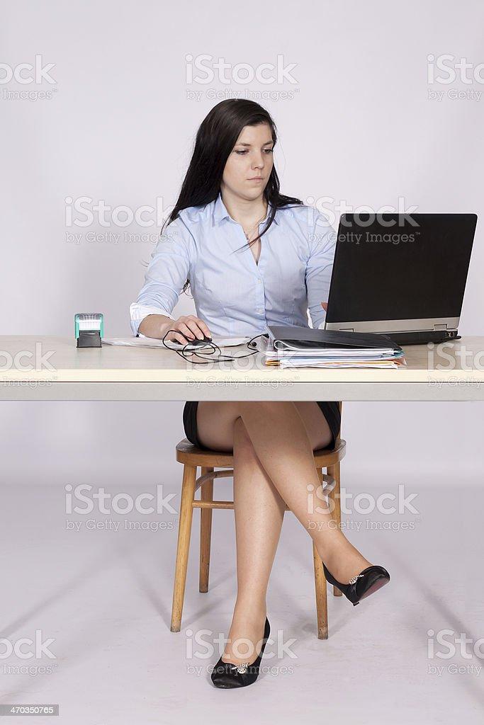 Weibliche Posen, die hinter einem Schreibtisch im Büro – Foto