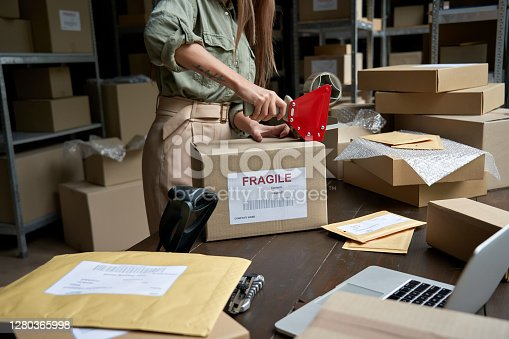 istock Female post mail storage worker holding tape dispenser sealing shipping online store order courier delivery cardboard box packing ecommerce fragile dropshipping parcel in distribution warehouse. 1280365998