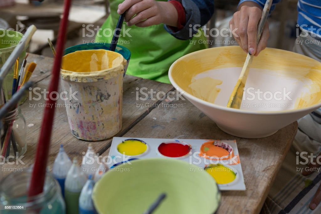 Female potter and boy painting bowl stock photo