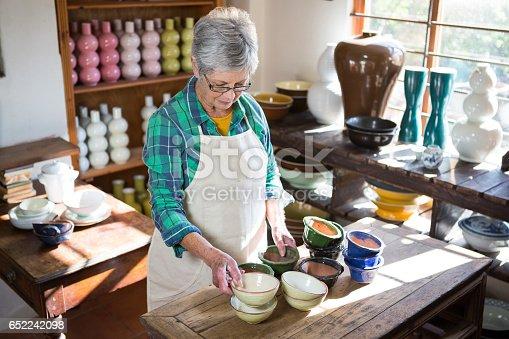 652188430 istock photo Female potter arranging bowl on worktop 652242098