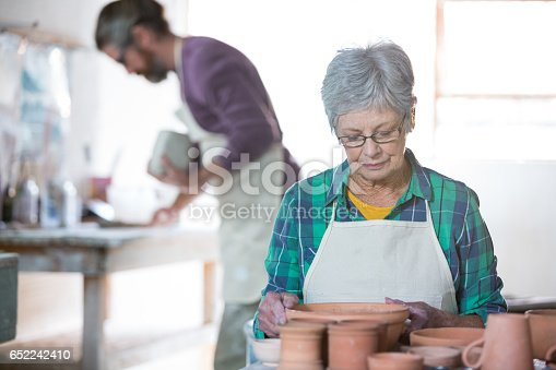 652188430 istock photo Female potter checking pots 652242410