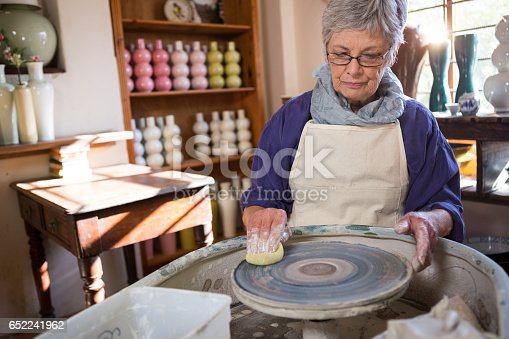 652188430 istock photo Female potter cleaning pottery wheel 652241962
