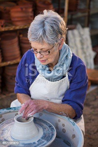 652188430 istock photo Female potter making pot 652235920