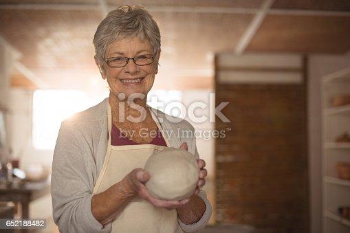 652188430 istock photo Female potter molding clay 652188482
