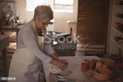 652188430 istock photo Female potter molding clay 652188576