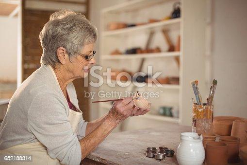 652188430 istock photo Female potter painting on bowl 652188314
