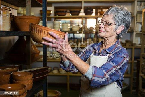 istock Female potter placing bowl on shelf 652242398