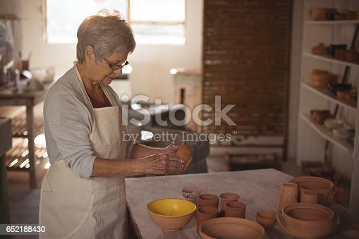 652188430 istock photo Female potter pouring watercolor in bowl 652188430