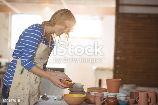 istock Female potter pouring watercolor in bowl 652197018