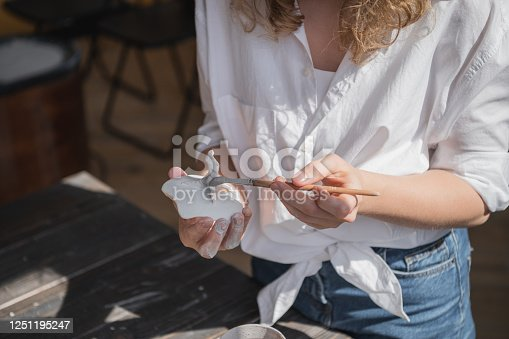 627000458 istock photo Female potter sitting and stirs paint with a brush a cup on the table. Woman making ceramic item. Pottery working, handmade and creative skills 1251195247