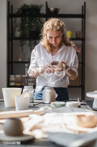 627000458 istock photo Female potter sitting and stirs paint with a brush a cup on the table. Woman making ceramic item. Pottery working, handmade and creative skills 1254446788