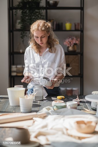 627000458 istock photo Female potter sitting and stirs paint with a brush a cup on the table. Woman making ceramic item. Pottery working, handmade and creative skills 1257093958