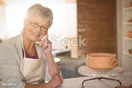652188430 istock photo Female potter sitting at table 652180734