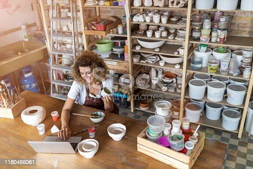 istock Female potter using laptop in art studio 1180466061