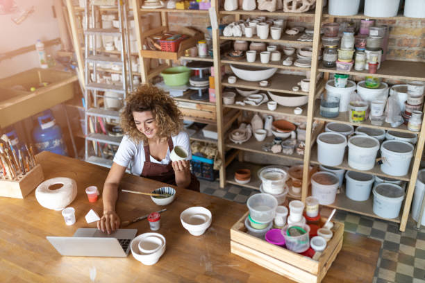 oleiro fêmea que usa o portátil no estúdio da arte - cerâmica artesanato - fotografias e filmes do acervo