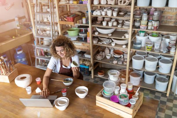 Weibliche Töpferin mit Laptop im Kunststudio – Foto