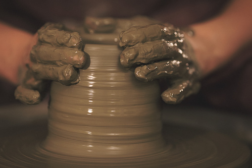 Female pottery artist making a shape from clay