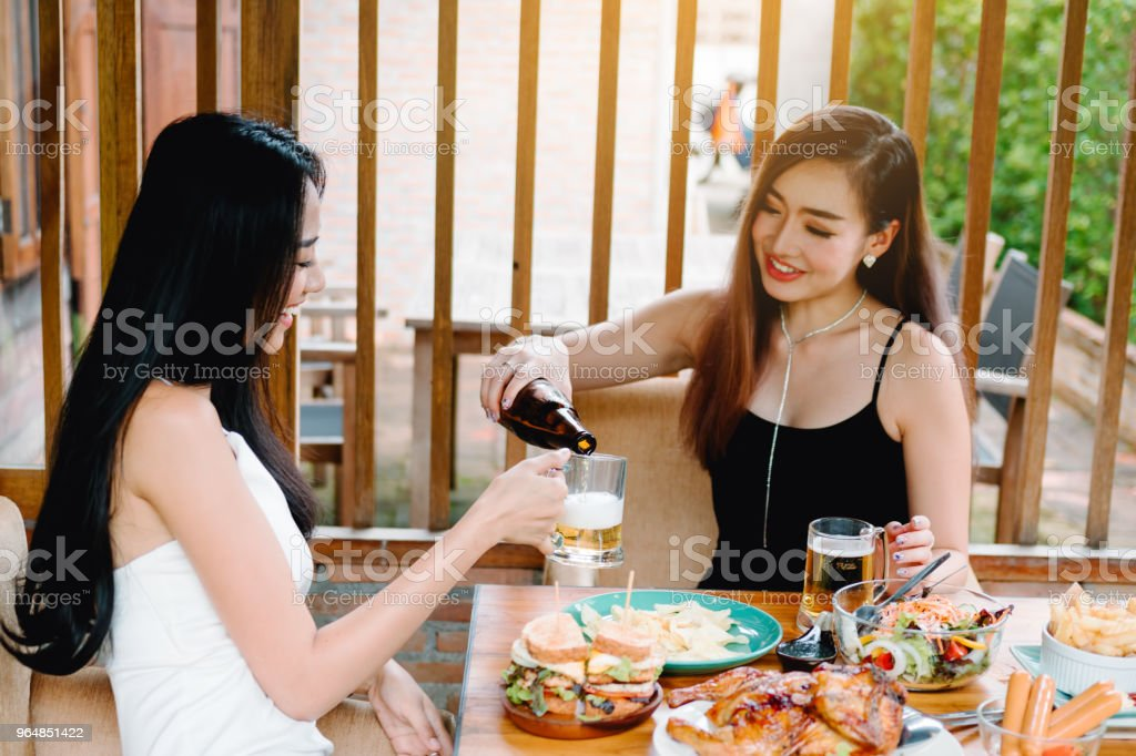 Female pouring beer in glass and drink together. royalty-free stock photo