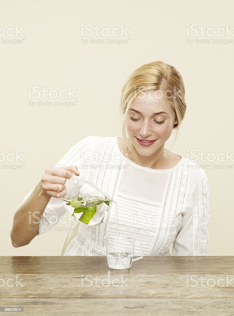 female pouring freshly brewed tea in glass foto de stock libre de derechos