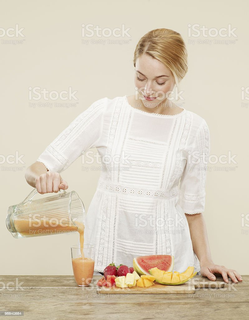 female pouring fruit smoothie into a glass photo libre de droits