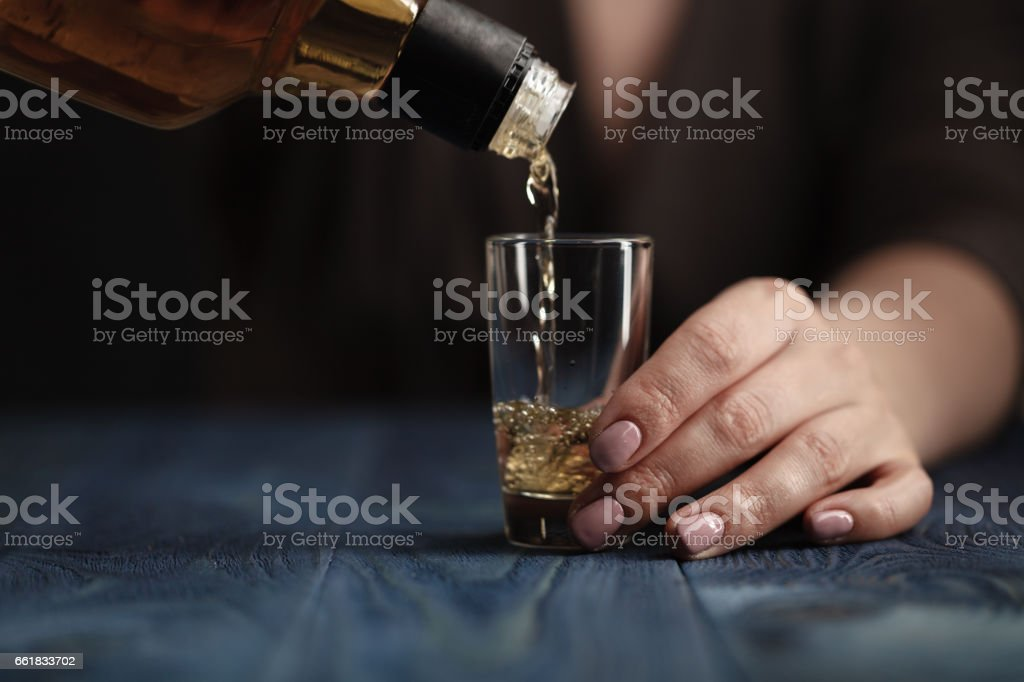 Female pouring whiskey in to glass shot – Foto