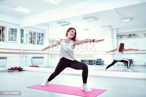 Female Practicing Lunge Exercise In Gym