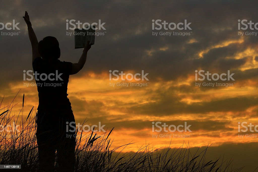female praying with bible stock photo