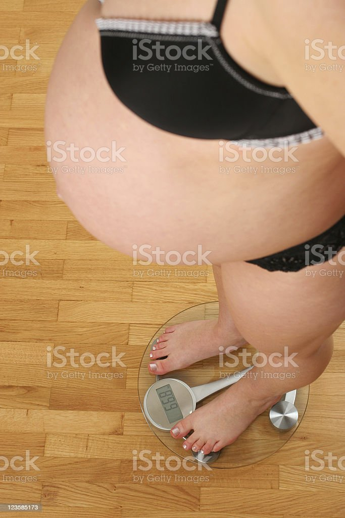 Female pregnant on bathroom scale royalty-free stock photo